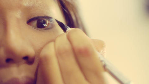 Young Thai Girl Applying eyeliner to top eyelid. Toned video Footage