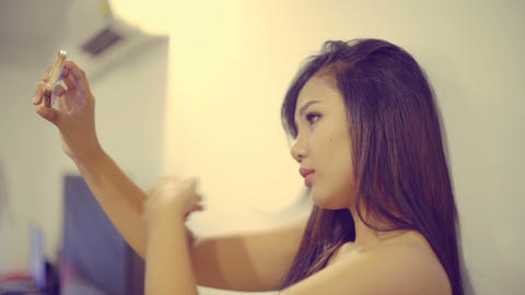 Young Asian Girl making selfie photo on smart phone. Toned video hipster filter Footage
