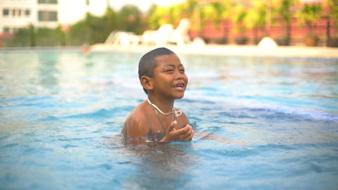 Happy boy diving in outdoor swimming pool slowmotion Footage