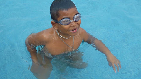 Little boy swims in outdoor swimming pool slowmotion Footage