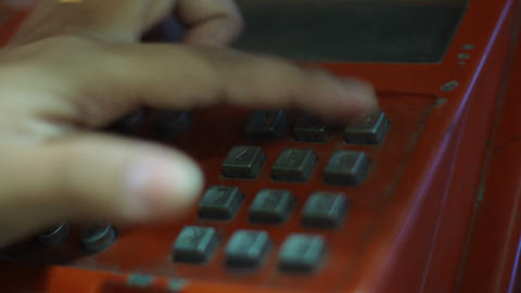 Dialing number on public phone in booth close-up Footage