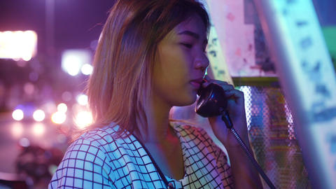 Young Woman talking on public telephone Live Action