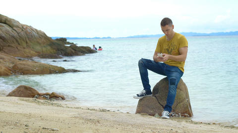 Young man with smartphone sitting on rock at beach Footage