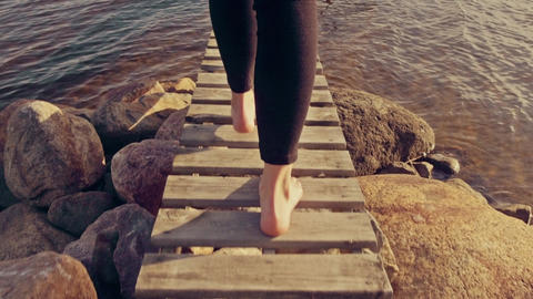 Young Woman Walking Out on Jetty in Slow Motion, Camera Following - Graded Look Footage