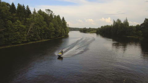 Girl and boy on the jet ski in the river.Aerial video Footage