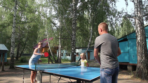 Dad and mom playing ping pong and daughter looking at the game Footage