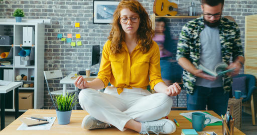 Time lapse of beautiful redhead woman relaxing in office in lotus position Footage