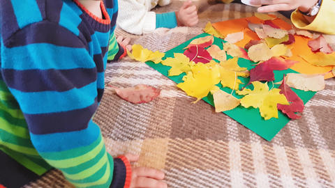 Young mother with children make autumn applique from autumn leaves. Little girl Live Action