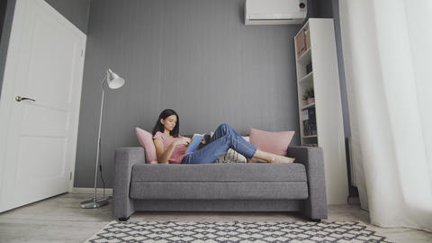 Sleepy woman lying on couch reading boring book at home. College girl student Live Action