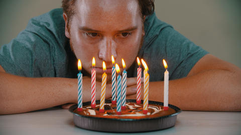 Sad man is blowing out the candles on the birthday cake Live Action