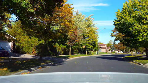 Rear View From Back of Car Driving Around Road Bend in Residential Suburb in Day. Car Point of View Live Action