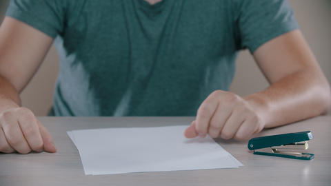 A man is fastening a paper by stapler Footage