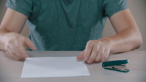 A man is nervously fastening a paper by stapler Footage
