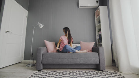 Woman leaving smartphone and relaxing sitting on a couch Footage