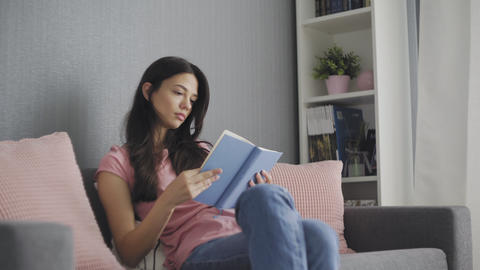 Beautiful attractive young woman reading a book while sitting on sofa at home Live Action