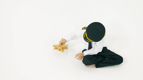 Boy wearing pilot's uniform plays with toy plane. Aircraft landing Live Action