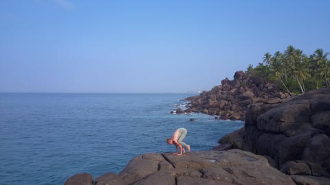 slim woman practices yoga position against tropical nature Live Action
