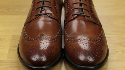 Approaching, pair of brown classic men's shoes standing on a wooden floor. Men's Footage