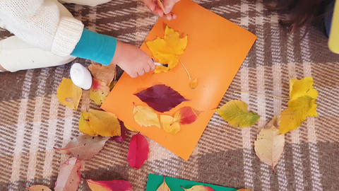 Mom and little daughter make autumn applique from autumn leaves. Little girl Footage