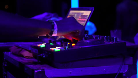 Close up of DJ twisting the knobs on his equipment at the party Live Action