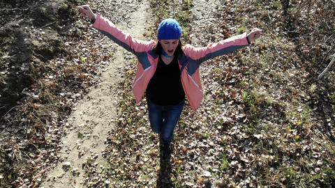 flying over happy woman dancing outdoors in autumn park, aerial shot, carefree Footage