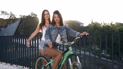 Cheerful Caucasian girls friends in trendy clothing with one bicycle walking in Live Action
