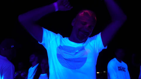 Close up of a man dancing at the party, ultraviolet open air party Live Action
