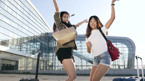 Cheerful beautiful young asian brunettes jumping from joy with air tickets in Footage