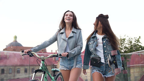Portrait of two young attractive urban women walking with a bike and Footage