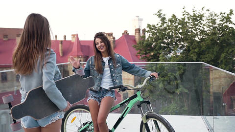 Attractive young girl with bike meets for her best female friend on in on the Footage