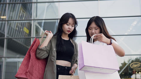 Two joyful likable young asian girlfriends standing near shopping mall and Footage