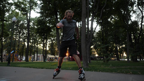 Young long-haired bearded man roller skater is dancing in a nice evening in a Footage