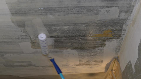 The ceiling is moistened with a transparent liquid using a roller on a pole Footage