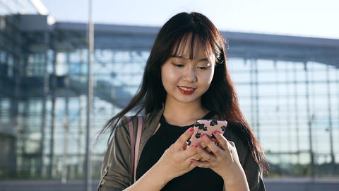 Pleasant carefree young asian woman typing sms on her phone near the airport Live Action