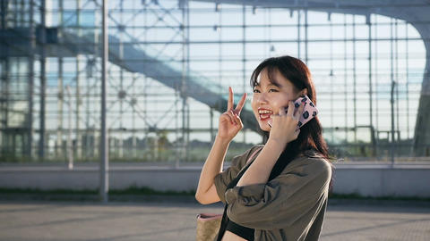 Appealing cheerful asian young woman talking on smartphone on the background of Footage