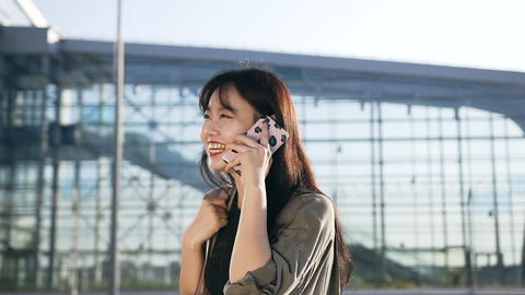 Pretty cheery young asian woman with dark hair talking on phone and sincerelly Footage