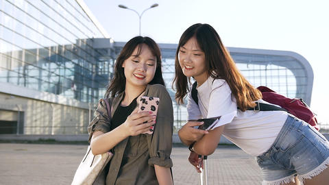 Charming cheerful 25s asian female travelers standing near modern airport and Footage