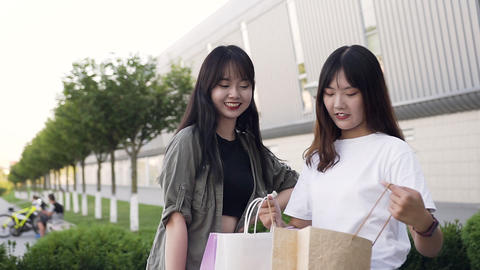 Charming happy young asian women revisioning purchases after shopping outdoors Footage