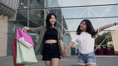 Attractive portrait of two happy good-looking asian girls dressed in modern Footage