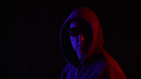 Portrait adult man in black sunglasses and hoodie turning around in studio on Footage