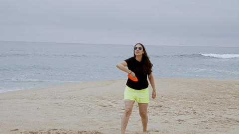 Beautiful girl has fun on the beach at the oceanfront - summer holiday Footage