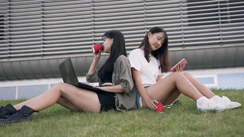 Two appealing young asian female best friends sitting on lawn back to back and Live Action