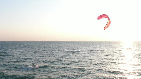 Kitesurfer is turning back to the beach, bright sunlight reflecting in the water Live Action