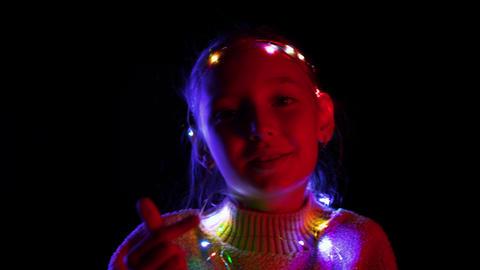 Happy teenager girl in glowing Christmas garland dancing in dark studio Footage