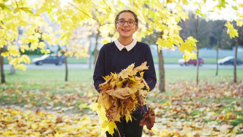 girl throws up leaves and having fun in autumn park Footage