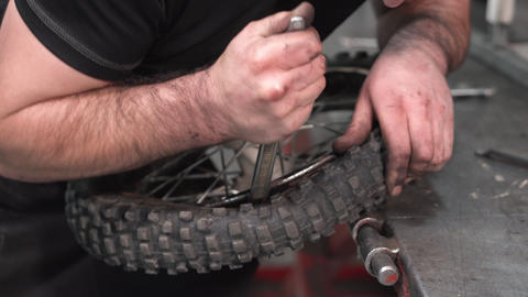 Mechanic repairing damaged motorcycle tire, in repair shop Live Action