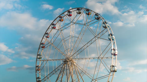 Timelapse of rotating ferris wheel and white clouds movement, sunset cloudy sky Footage