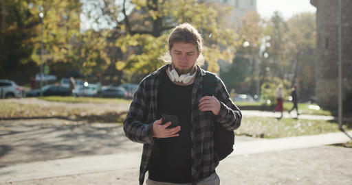 Young man using his phone as he walks on the street. Man is using his Smartphone Footage