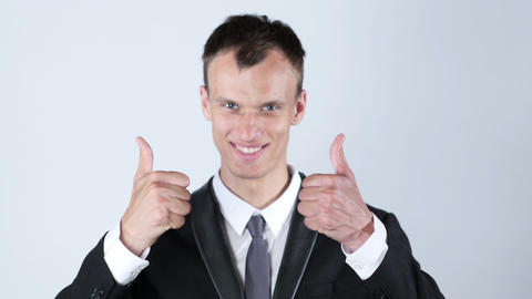 young business man shows thumbs up with both hands while smiling Footage