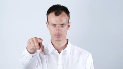 man wearing white shirt points at camera , white background Footage